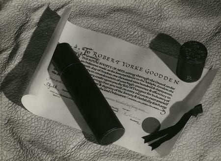 Black and white photograph of the Diploma of The Faculty of Royal Designers for Industry awarded to Robert Yorke Goodden.The leather scroll case is placed on top.