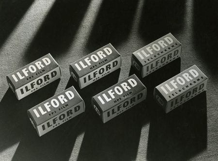 Black and white photograph showing 6 boxes of Ilford film, 2 each of FP3, HP3 and Selochrome.