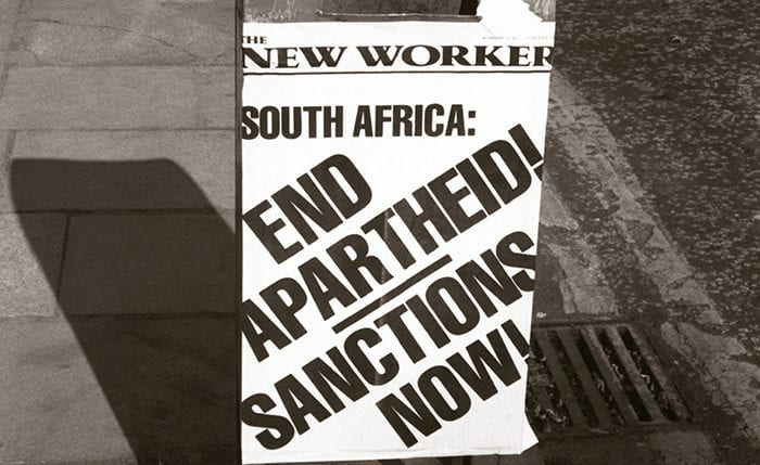 Black and white photo of litter bin with ad for The New Worker - South Africa: End Apartheid! Sanctions Now!