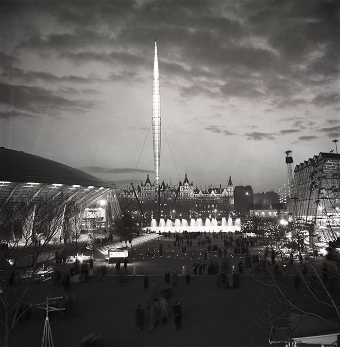 Black and white photo of Festival of Britain showing view of Skylon with pedestrians at dusk. Dome of Discovery on the left.