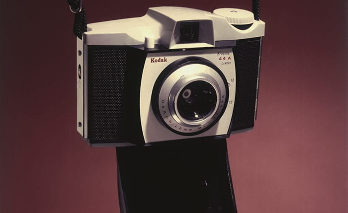 A Kodak Brownie 44A camera with the case open showing the lens hanging by it's straps against a dark red background.
