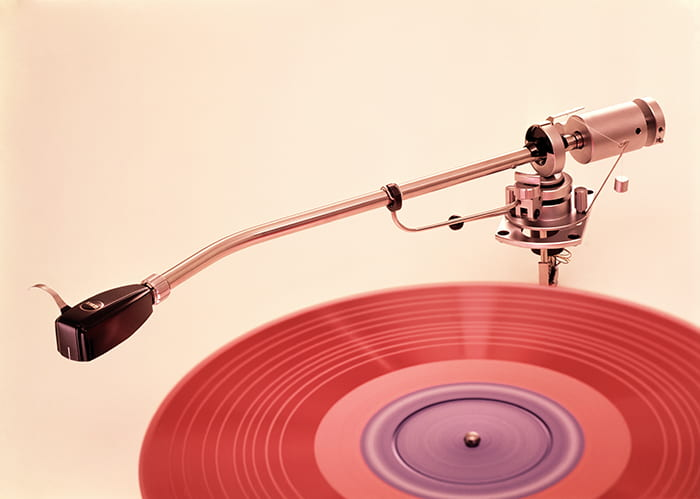 Image shows a record player pick-up arm over a pink vinyl record with a purple centre.