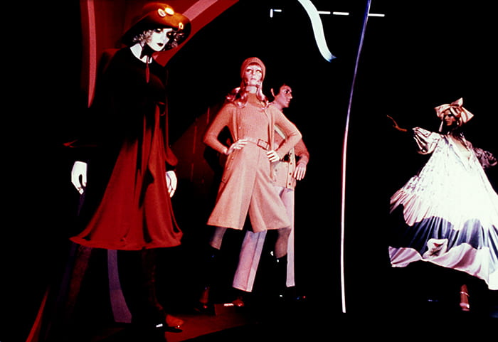 Image shows four mannequins arranged across the frame. From left side wearing red dress and hat, beige coat and hat, not fully visible and puffy white dress and head wrapping.