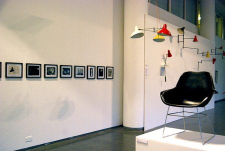 Installation view showing framed photographs on front left wall, coloured lampshades hanging from ceiling and on back left wall and black plastic moulded chair on a white plinth front right.