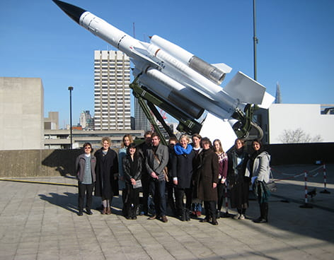 Group of people posing in front of a rocket