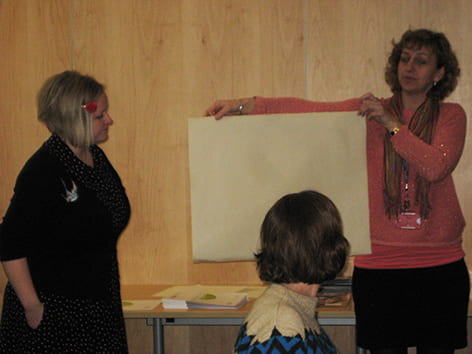 Two presenters showing workshop attendees a piece of hand made paper