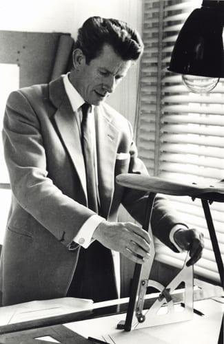 Black and white portrait of Robin Day measuring a chair leg angle