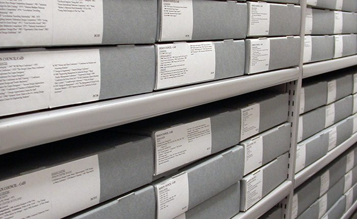 Grey archival boxes with white printed labels neatly placed on an archive shelf at the University of Brighton Design Archives