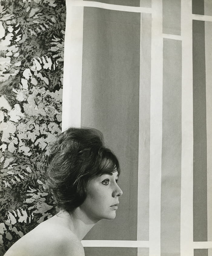 Black and white portrait of Shirley Craven in front of her fabric designs