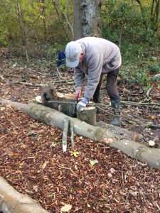 John cuts pointed stakes to keep the edge logs in place