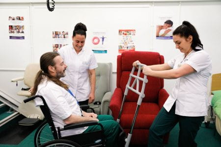 Three occupational therapists practicing with tool to help with wheelchairs