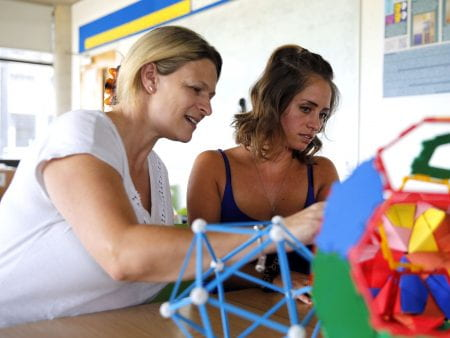 Two people construct a colourful model