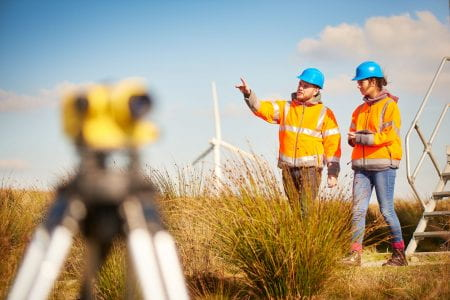 Two people with high visibility jackets and hard hats, in a field