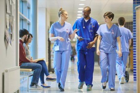 Image of three medical professionals walking and talking