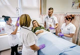 Image of four nurses standing around a patient