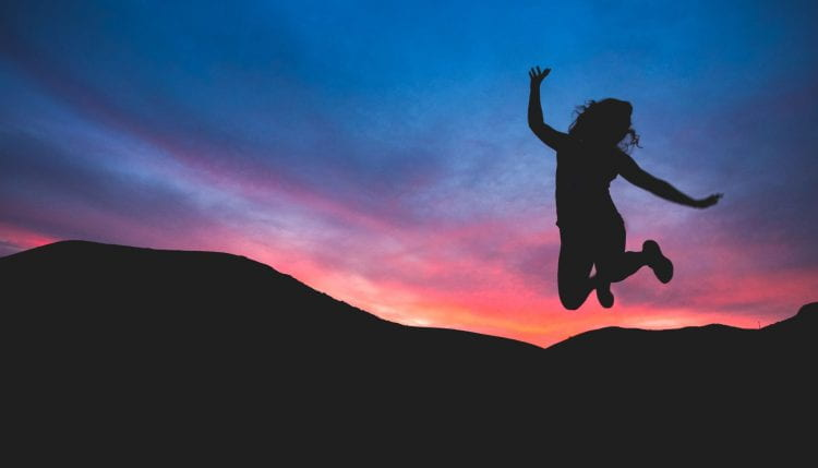 silouette of someone jumping in front of a sunset