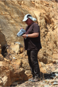 Professor David Nash using the PXRF to analyse the rock outcrops in the landscape surrounding the site of Isimila.  Photograph courtesy of Professor David Nash