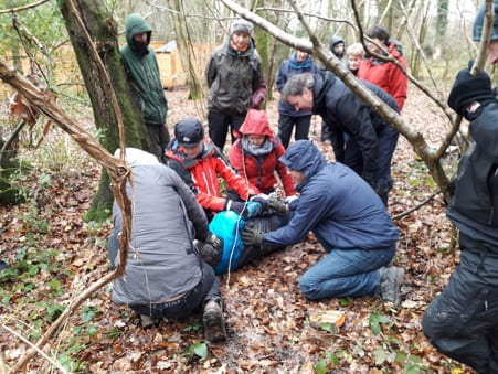 Group with man lying on floor in forest