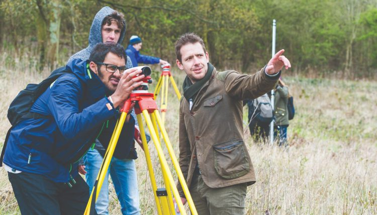 Two students conducting fieldwork in a field with lecturer