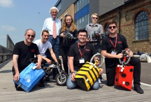 Lord Baker with (front row) Ian Watts, Ryan Pratt and Darren Harkin of University of Brighton with their Creepy Crawlie Battlebots and, behind them, Kyle Brackenfield on his electric motorbike, Sophie Lewis and Keeran Gillett with VEX robotic cars.