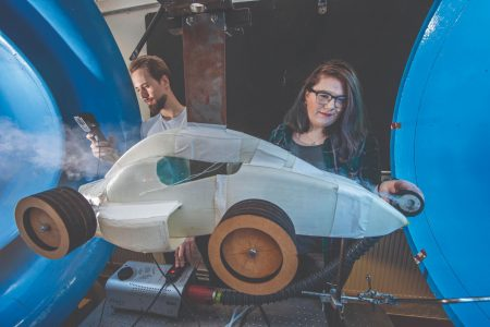 Female and male student using wind tunnel to test a model car