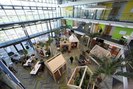 Image shows high view of wooden structures where students can work in the atrium of Checkland