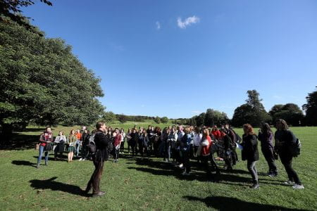 The image is of a man addressing a crowd of students in a countryside setting
