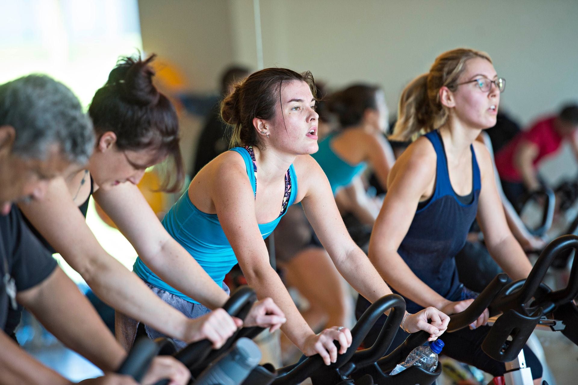 People on cycle machines in a gym.