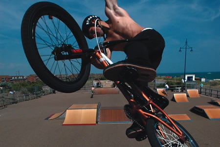 Guy riding a BMX in a bike park.
