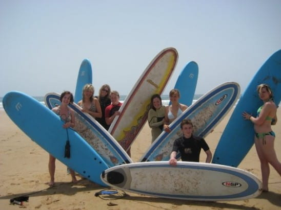 A group of people posing on a sandy beach with surfboards.