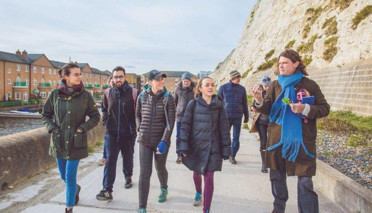 Students walking alongside Brighton cliffs