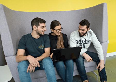 Three university students sharing a laptop