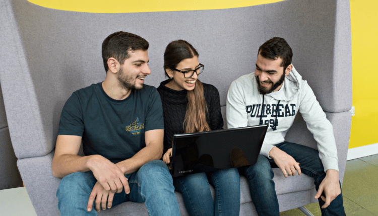 Students sitting around a laptop