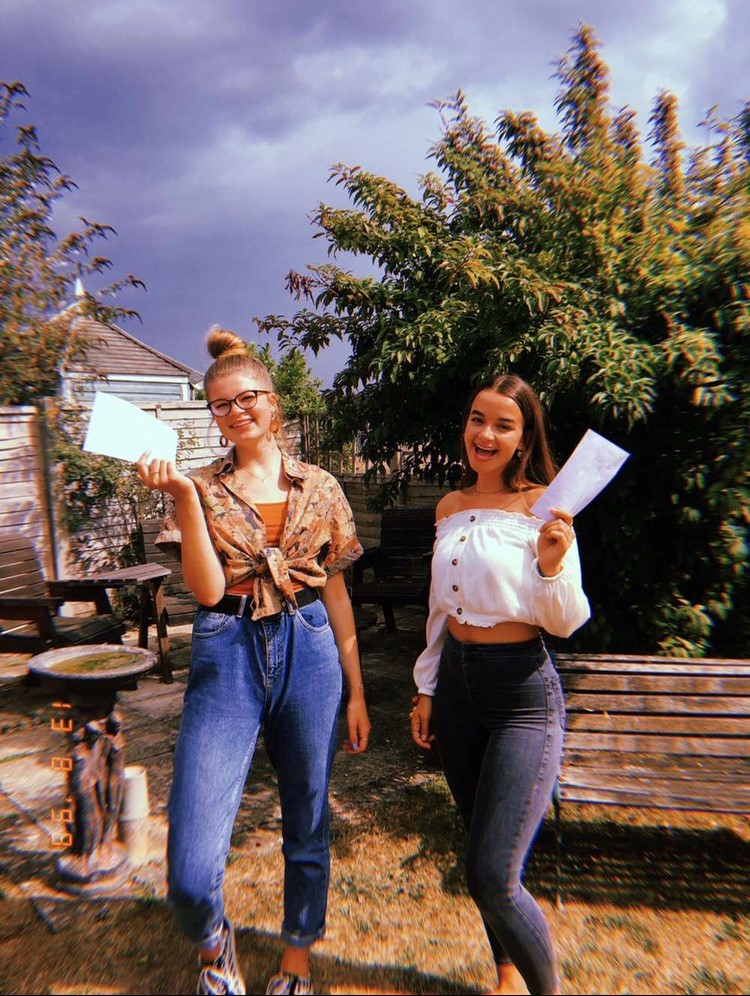 Jenny and a friend holding their results