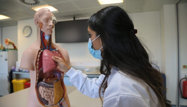 Thivya using a mannequin to study medicine