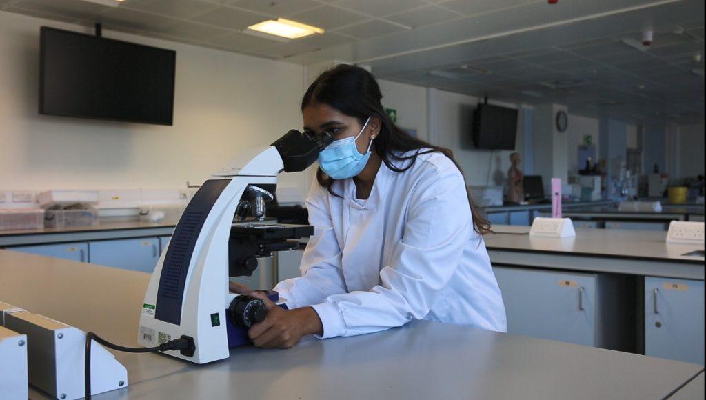 Thivya looking through a microscope