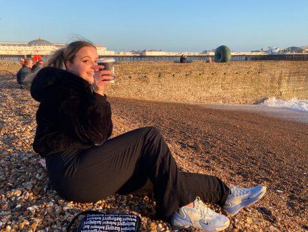 Viktorija sitting on Brighton beach