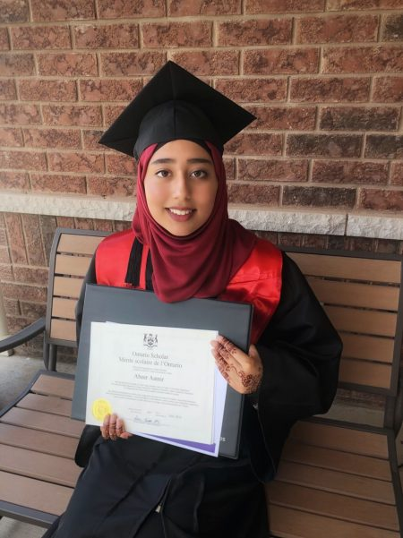 Abeer smiling at the camera with her graduation certificate!