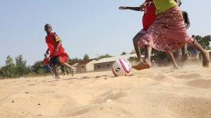 children playing football in the desert