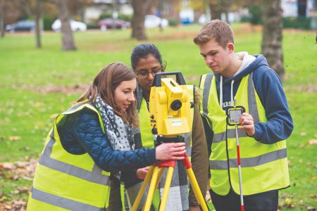 Three students outside in high vis jackets using a total station