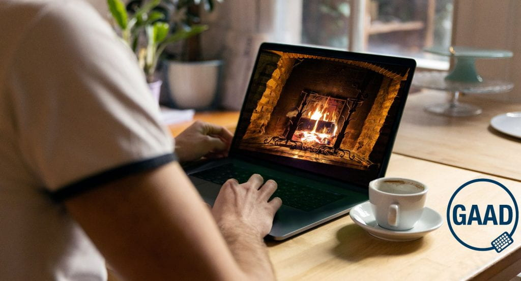 Person using a laptop at a table with an espresso cup on the right. On the laptop screen a roaring fire is shown onscreen
