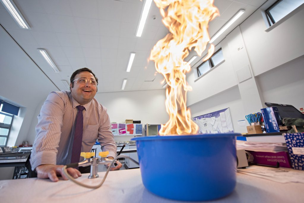 an image of a teacher in a science lab - he has a bowl full of flames in front of him