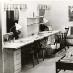 A black and white photo of a childrens room setting with bunk beds and desks