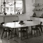 A black and white photo of nursery furniture setting with table and chairs