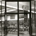A black and white photo of an outside view of the grocery department showing fruits in baskets