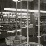A black and white photo of a grocery shop setting with goods displays on the walls