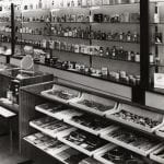 A black and white photo of a perfume shop setting with bottles on shelves