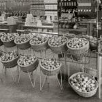 A black and white photo of an interior view of a grocery shop and its fruit display
