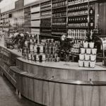 A black and white photo of a grocery department store setting with curved counter