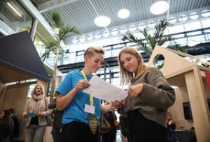 A student helping speaking to a guest at Falmer open day